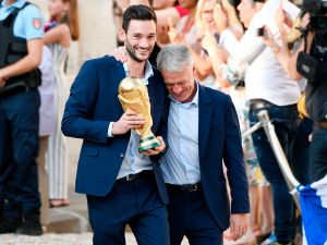TOPSHOT - France's goalkeeper Hugo Lloris (L) smiles and holds the trophy next to France's coach Didier Deschamps as they arrive for a reception at the Elysee Presidential Palace on July 16, 2018 in Paris after French players won the Russia 2018 World Cup final football match. - France celebrated their second World Cup win 20 years after their maiden triumph on July 15, 2018, overcoming a passionate Croatia side 4-2 in one of the most gripping finals in recent history.