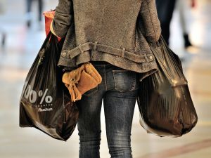 "A woman carries so-called ""single-use"" shopping bags as she exits a shopping centre in Faches-Thumesnil, northern France, on June 27, 2014. A governmental amendment added to the biodiversity bill on June 25, aims for a total ban on single-use plastic bags."