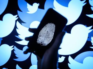 In this photo illustration, a thumbprint is displayed on a mobile phone as the logo for the Twitter social media network is projected onto a screen on August 09, 2017 in London, England. With around 328 million users worldwide, Twitter has gone from a small start-up in for the public 2006 to a broadcast tool of politicians and corporations in 2017.