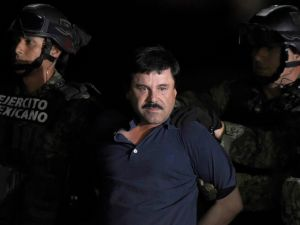 "Drug kingpin Joaquin ""El Chapo"" Guzman is escorted into a helicopter at Mexico City's airport on January 8, 2016 following his recapture during an intense military operation."