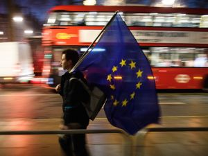 A man carries a European Union flag outside the Supreme Court in Parliament Square ahead of the ruling on whether Parliament have the power to begin the Brexit process, on January 24, 2017 in London, England.