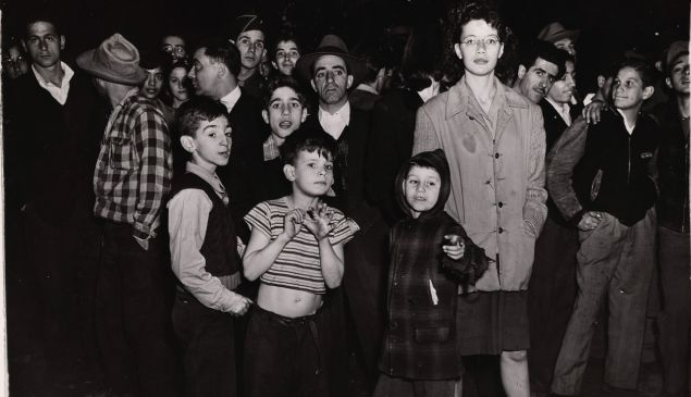 A crowd of men, women and children gathers at the scene of a murder on Manhattan's East Side, New York, circa 1940.