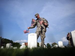 Members of the 3rd U.S. Infantry Regiment place American flags at the graves of U.S. soldiers buried in Section 60 at Arlington National Cemetery in preparation for Memorial Day.