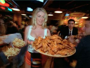 A Hooters waitress serves a large platter of chicken wings.
