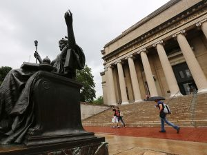 People walk past the Alma Mater statue on the Columbia University campus in New York City.