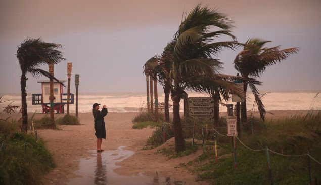 A woman takes a picture as the effects of Hurricane Dorian begin to be felt on September 2, 2019 in Cocoa Beach, Florida.