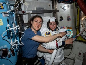 NASA astronaut Christina Koch (left) poses for a portrait with fellow Expedition 61 Flight Engineer Jessica Meir of NASA who is inside a U.S. spacesuit for a fit check.