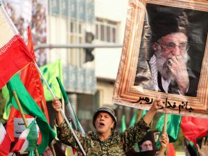 "A man dressed in a military uniform chants slogans as Iranian pro-government demonstrators raise national flags and a picture of the Islamic republic's supreme leader, Ayatollah Ali Khamenei, during a rally in the capital Tehran's central Enghelab Square on November 25, 2019, to condemn days of ""rioting"" that Iran blames on its foreign foes."