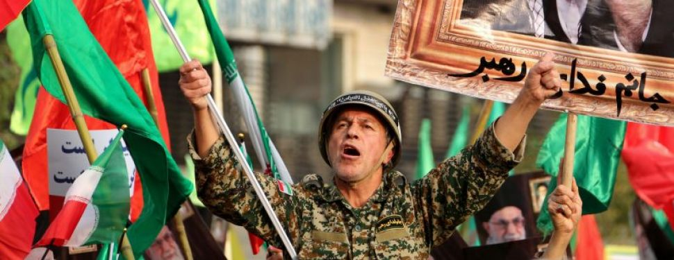 """A man dressed in a military uniform chants slogans as Iranian pro-government demonstrators raise national flags and a picture of the Islamic republic's supreme leader, Ayatollah Ali Khamenei, during a rally in the capital Tehran's central Enghelab Square on November 25, 2019, to condemn days of """"rioting"""" that Iran blames on its foreign foes."""