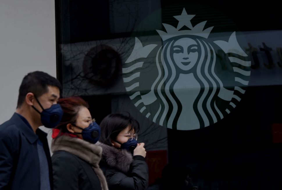 People wearing protective face masks walk past a closed Starbucks coffee shop in Beijing on January 29, 2020.