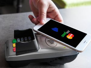 Woman paying with mobile phone.