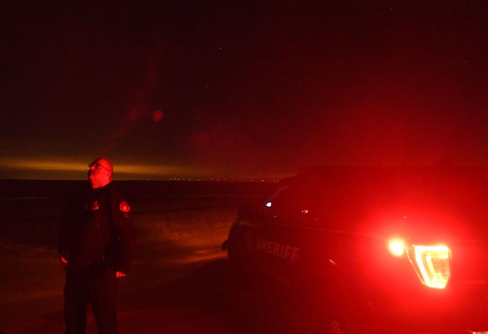 Lincoln County Sheriff Deputy Justin Allen stands outside of his squad car looking up at the night sky on January 2, 2020 near Limon, Colorado. The Lincoln County Sheriff's office had been working with surrounding counties to figure out who is behind the mystery drones flying overhead.