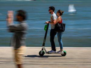 A couple ride an e-scooter—sans helmets and dangerously close to the Tagus River—on June 12, 2019 in Lisbon, Portugal.