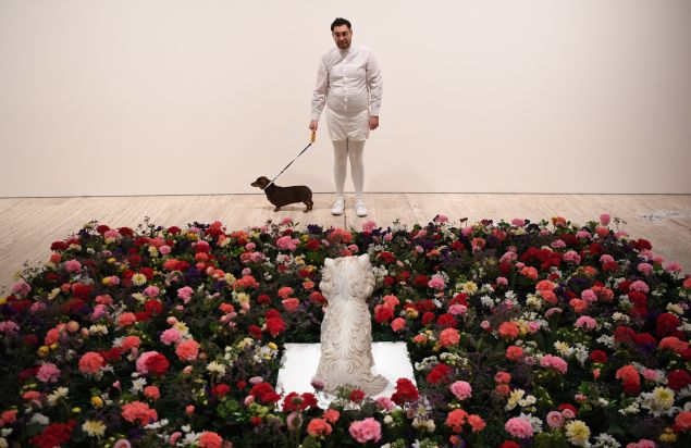 "The artist David Capra with his sausage dog, Teena, looking at ""Puppy"" by Jeff Koons."