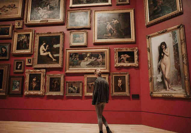 Woman in a gallery peruses art made by men.