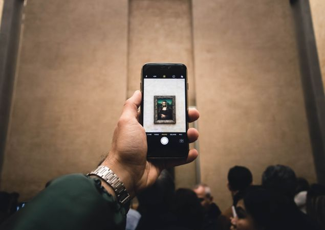 A visitor to the Louvre looking at an image of the Mona Lisa.
