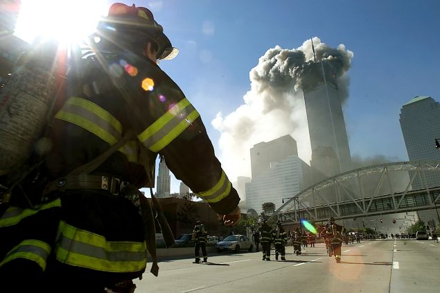 Firefighters walk toward New York's World Trade Center before it collapsed after a plane hit the building September 11, 2001