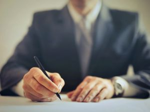 crop-businessman-signing-contract-in-office-3771097
