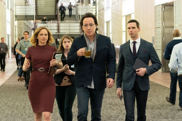 John Cusack (center) and Cory Michael Smith (right) in Utopia